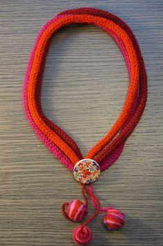 Collana eseguita a mano con l'uncinetto e realizzata in lana; bottone in legno decorato e pendenti in lana cotta. Diametro collana esclusi pendenti 20 cm. http://www.flickr.com/photos/gioiedilillo/   http://www.misshobby.com/lill