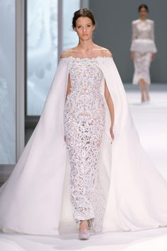 White sheer tulle gown with silk crêpe cape and guipure lace and glass bead embellishment.