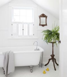In this century-old Oregon farmhouse, an ornate Eastlake plant stand pops against the bathroom's spare Rejuvenation tub and white subway tiles.   - CountryLiving.com