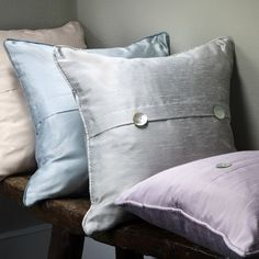 Clarke and Clarke -  Emperor Fabric Collection - Plain cream cushion, pale blue cushion, grey cushion, and lilac cushion, all silk effect and with two buttons for added detail