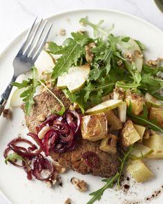 Een mooi bordje vol met een sappige steak en daarbij heerlijk zoete balsamico-uitjes, knapperige ovenpatatjes en een frisse salade met peer, walnoten en rucola.