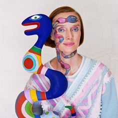 The French sculptor, painter and film-maker, Niki de Saint Phalle (1930 - 2002), photographed with one of her sculptures.