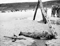 soldier lies on the sand of Omaha Beach killed by German fire on D-Day as U. troops finally capture and secure the beach. The crossed rifles at his feet were put there to form a battle cross Omaha Beach Normandy France 6 June Battle Of Normandy, D Day Normandy, Normandy France, Normandy Invasion, Normandy Tours, Normandy Ww2, Normandy Beach, M1 Garand, Omaha Beach