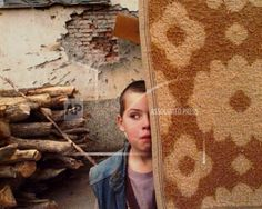 A young Bosnian refugee is hesitant to come out from behind a carpet as a UN convoy arrives in the UN protected enclave of Gorazde,  Dec. 9, 1995.  (AP Photo/John Gaps III)