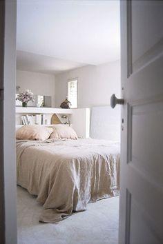 chambre sol béton beige, porte blanche, linge de lit en lin, tête de lit blanche avec étagère