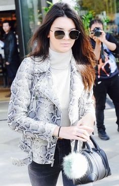 Kendall Jenner wears a turtleneck, snake-print moto jacket, high-waisted jeans, a mini Givenchy duffle bag, Ahlem aviator sunglasses, and a Fendi pompom bag charm