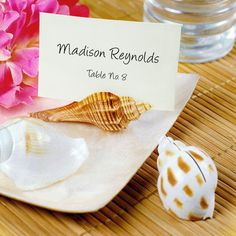 Real, natural seashells make the perfect place card holders and table decorations for a beach themed wedding or ocean-side event.