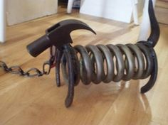 This is a dog made out of an old shock absorber, two horse shoes and a hammer head