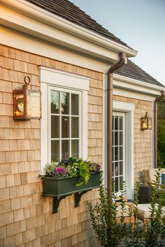 "Window boxes add a lively arrangement of color to the cedar siding. ""The window boxes are very much a part of the Vineyard experience, and pertain to what is happening in each room so you look out and they are color coordinated,"" explains interior designer Linda Woodrum."