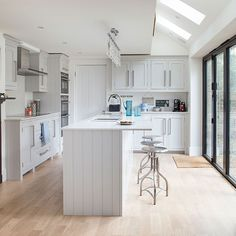 This bright Shaker-style kitchen has an open-plan design that features an island unit and oak flooring. There are a trio of stools that help make this a sociable and fun environment to be in