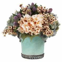 "With silk wildflowers in an eye-catching ceramic pot, this lovely arrangement brings a touch of natural style to your decor.   Product: Faux floral arrangementConstruction Material: Silk, plastic and ceramicColor: Aqua, green, purple and cremeFeatures: Includes faux hydrangeas and thistlesDimensions: 14"" H x 15"" Diameter"