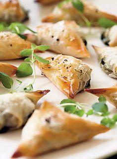 Käteensopivat fata-pinaattikolmiot ovat mainio piknikeväs tai juhlapöydän suolainen pikkuherkku! Ohuen filotaikinakuoren sisään kätkeytyy mehevä feta-pinaattitäyte.