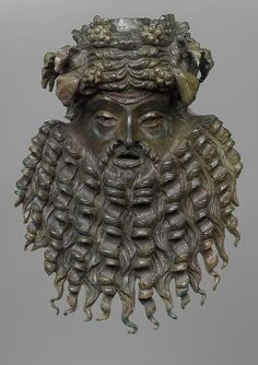 Bacchic Mask    Bronze    Roman, 1st Century AD    The ivy wreath is clearly visibly on the head complete with bunches of grapes. His long beard is beautifully rendered, fanning out in twisted corkscrews.