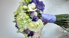brides handtied of avalanche roses, white freesia, memory lane roses, purple lissianthus, and green carnations