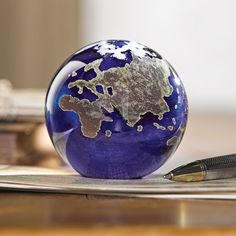 This collectible art glass globe paperweight by Lundberg Studios depicts an abstract version of Earth for your home office. Lundberg Studios Art Glass Globe Paperweight | National Geographic Store