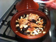 Zo ziet de tajine eruit met de kip er weer in, bestrooid met de pruimen en de amandelen.
