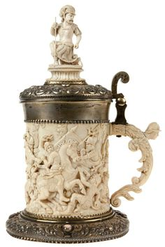 Ivory, silver and silver plated metal mounted tankard. The cylindrical body elaborately carved with a cavalry scene. The handle with a helmeted term figure. Finial in a shape of a kneeled general. Mounts chased with fruits and foliage and set with decorative stones. 19th century German work.