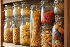 Kitchen storage jars stacked up with pretty pasta and pulses.