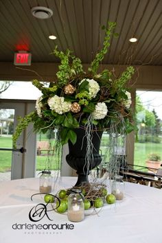 Wedding Table Arrangement by Village Vines Floral and Event Design.  Bells of Ireland, hydrangeas, hanging moss, green apples and dried pods.  www.villagevinesflorists.com