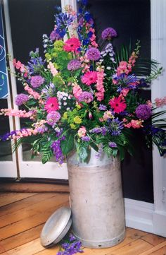 Wedding flowers for a Country style venue with a very modern twist milk churn hot pinks blues and greens Hograths hotel West Midlands