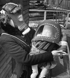 From the archives of LIFE magazine, mother and baby wearing gas masks during gas preparations test during WWII. Photo Credit: Hand Wild.