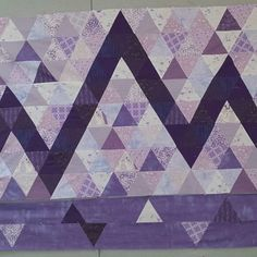 """My (only!!) #wip for @amyscreativeside's #igquiltfest is titled """"Purple Mountain Majesties."""" Those damn pyramids are giving me so much grief, I can't wait to move on to something else. I still have to work out what to do with the more improv-style top and bottom borders, but I'm hoping to start quilting next week."""