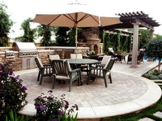 Plenty of stacked stone, vine-covered columns and a circular cobblestone patio give this space a lovely Tuscan flair.
