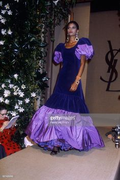 A fashion model wears a purple velvet haute couture evening gown with ruffles and puffed sleeves by French fashion designer Yves Saint Laurent. She modeled the gown during his autumn-winter Get premium, high resolution news photos at Getty Images 80s Fashion, Fashion History, Timeless Fashion, Fashion Models, Fashion Show, Fashion Brands, Yves Saint Laurent Designer, Yves Saint Laurent Paris, St Laurent