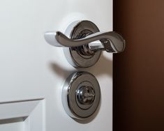 Polished chrome door handles on a bespoke bathroom internal door