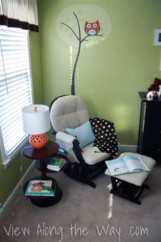 Green boy nursery with owl mural and orange lamp