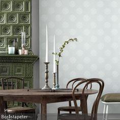 Das Highlight in diesem Retro-Essbereich mit Bistrostühlen ist der grüne Kachelofen. Passend dazu: die Tapete mit blassgrünem Muster. …