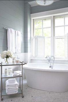 standalone tub under window gray paneled walls