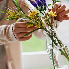 ENSIDIG Vase aus Klarglas mit einem Arrangement aus Frühlingsblumen.
