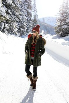 5 Stylish Snow Outfit Ideas: Fashion blogger 'Atlantic-Pacific' wearing a red pom pom beanie, a military parka, a red plaid shirt, a grey tunic sweater, black leggings, brown snow boots and black cat eye sunglasses. Casual outfit, snow outfit, snow day outfit, winter outfit, rain day outfit, comfy outfit, skiing trip outfit, cold weather outfit, cozy outfit, winter layers.