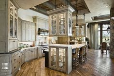 A spacious kitchen with selective sections of exposed beam, a curved island, and rustic cabinetry. Source: https://www.zillow.com/digs/Home-Stratosphere-boards/Luxury-Kitchens/