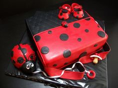 Lady bug diaper cake with RKT lady bug gumpast pacifier and lady bug shoes. Cake is chocolate with banana filling.