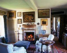 Room of the Day ~ Robert Kime ~ Sporting and equestrian paintings and prints cover the walls of this cosy sitting room which has a roaring log fire - love the art, rugs, tiled fireplace, fabrics... 6.22.2013