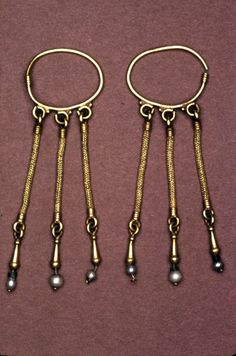 Earring; gold; consisting of a loop from which hang three strands of loop-in-loop gold wire; attached to each strand is a tear-shaped pendant with a pearl on a wire thread; one of a pair. Early Byzantine   Date:    6thC-7thC  Materials:    pearl, gold   Length: 89 millimetres