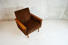 A very comfortable and elegant archair upholstered in amazing thick corduroy fabric in a rich dark brown. Teak armrests and tapered legs   Designer: unknown Manufacturer: Unknown Material: teak Country of origin: UK Size: Width 72 depth 77 height 75 seat height 38  cm          Date: 1960's Condition: Very good vintage condition. Signs of wear consistent with age and use. Some scuffing on front end of both armrests (price reflects this) Detailed photos available on request.
