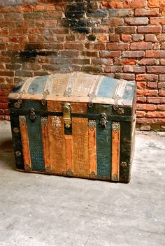 Love this vintage trunk--the shape, the color...even against the brick background.
