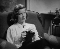 Linda Seton, played by Katharine Hepburn, knits while her father speaks with her sisters fiancé.