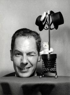 Theo Sanders   Opname van de beroemde goochelaar Fred Kaps (1926-1980). Zijn hoofd steekt boven een tafel met kleed uit en hij maakt een knipoog, op tafel staat vlak naast zijn hoofd een miniatuurkapstokje met drie hoeden eraan en een speelgoedkonijn in de mand ervan. Nederland, 1966.