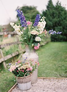 Two milk churns at the entrance to the marquee with foxgloves, Roses, Cow parsley.... seasonal country flowers