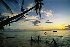 Niños jugando bajo una palmera en Betio, Tarawa, foto de George Steinmetz
