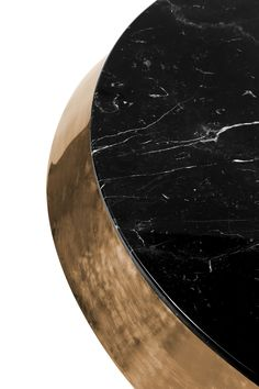 Miller is a stunning rotating cocktail table with gold plated brass rings over the four layered nero marquina marble discs. The metal provides dynamic contrast to the rich black marble and its rotation evokes a certain playfulness and style. Center your retro chic living room with this sober and provocative coffee table.