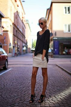 zipper miniskirt, black buckle sandals, loose black top, a simple necklace, and aviator sunglasses
