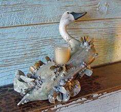 """""""Swan Candle"""" by Kevin Collins- Nautical- Marine Art. Virginia artist Kevin Collins re-purposes this old carved wood swan into a unique candle holder, decorated with applied handcrafted porcelain oysters, barnacles and other bay creatures. Measures 12 in. long X 11 in. tall and 7 in. deep. Great tabletop original art piece for your coastal home. Comes with 2 inch unscented candle in glass holder."""
