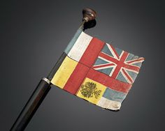 World War I Allies Flag Cane - This extremely rare walking stick is one of outstanding historical importance. A gentle pull on the basket-weave motif knob handle reveals a delicate flag of woven fabric, which bears the colors of the European Allies of World War I circa 1915, Great Britain, France, Belgium and Russia.   Circa 1915