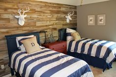 Wood feature walls. Woodland themed boys room. Shared space, two twin beds. New cedar planks, stained to look like salvaged wood. Simple how-to for this much cheaper version of reclaimed wood.  Red dresser acting as a nightstand, white deer heads above each bed. Theraggedwren.blogspot.com