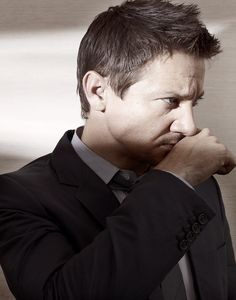 Jeremy Wearing Striped Shirt, Black Suit and Tie With Right Hand Held Up To His Face For a Photoshoot for GQ in Japan